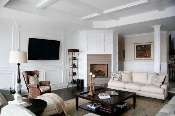 Камин расположен в углу, а телевизор на стене в гостиной