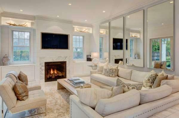 белая мебель в гостиной с зеркалами на стенах