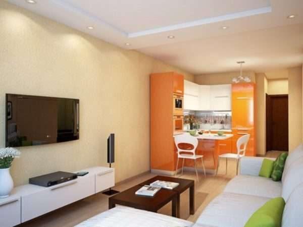 угловой кухонный гарнитур апельсинового цвета в интерьере кухни гостиной 17 кв. м
