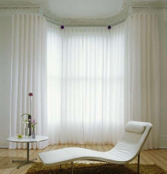 полупрозрачные занавески в интерьере гостиной с эркером