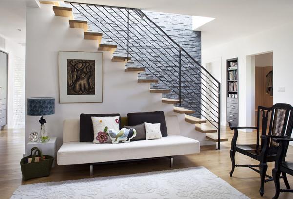 лестница одномаршевая в интерьере гостиной с обустройством зоны отдыха под ней