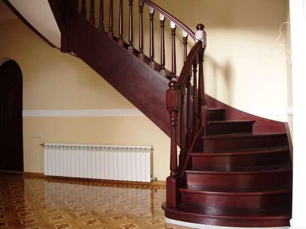 деревянная лестница с поворотом в интерьере гостиной