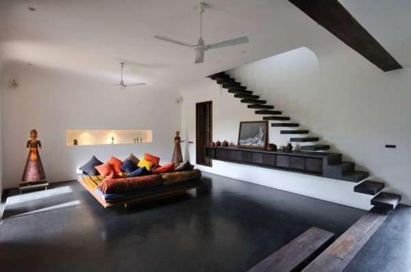 лестница в интерьере гостиной с размещением модульной мебельной стенки под собой