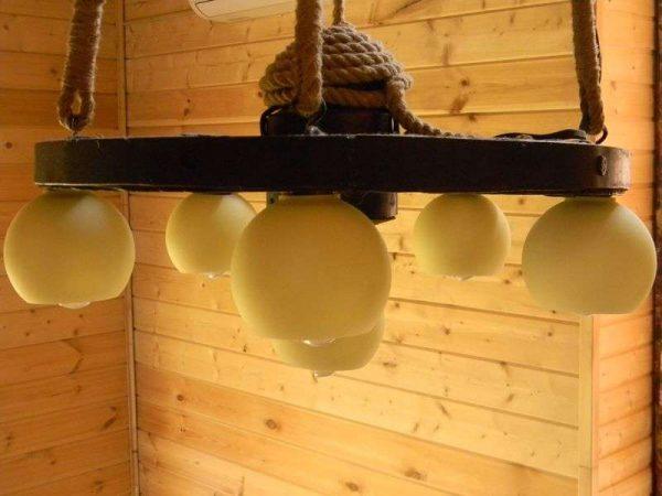 гостиная в деревянном доме с люстрой из колеса