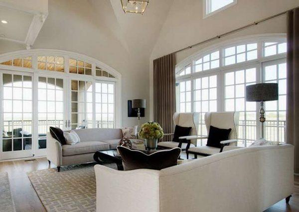 коричневые шторы в интерьере гостиной с огромными арочными окнами