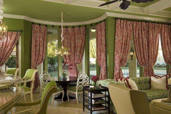 красные шторы в интерьере гостиной с зелёными стенами