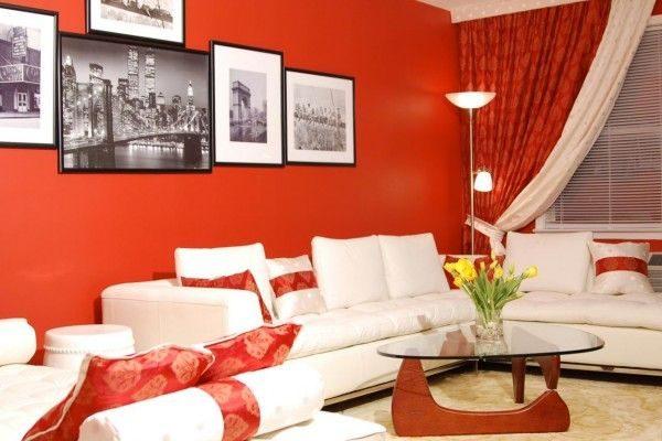 красные шторы в интерьере гостиной с белой мебелью и красными стенами