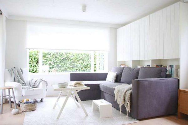 интерьер светлой гостиной с серым диваном после ремонта