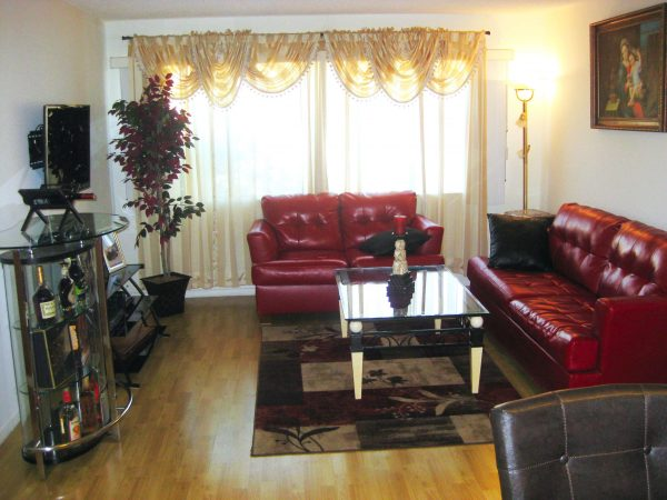 интерьер гостиной после ремонта с красными кожаными диванами