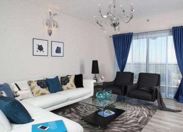 синие шторы с прозрачными гардинами в интерьере современной гостиной