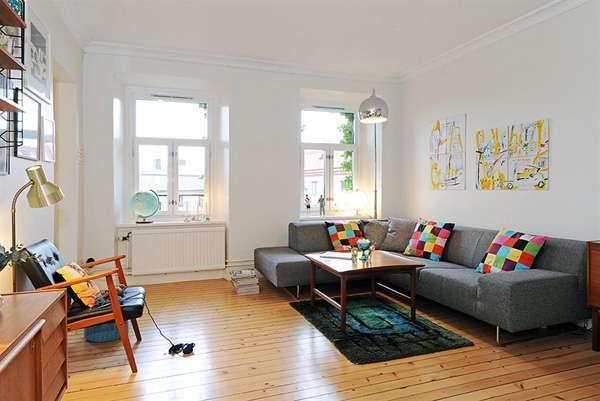 в интерьере гостиной в скандинавском стиле серый диван с декоративными подушками