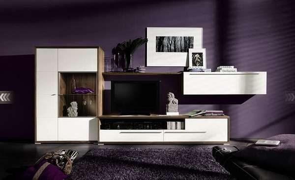 белая мебельная стенка в интерьере гостиной с фиолетовыми стенами