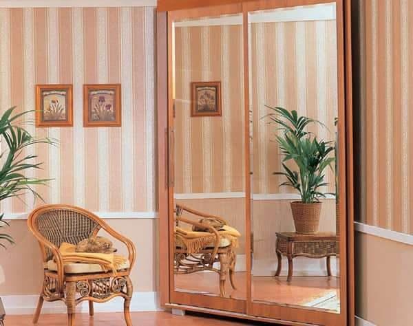 небольшой угловой шкаф в интерьере гостиной с зеркалом