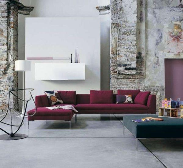 угловой диван бордового цвета с открытыми ножками в интерьере гостиной