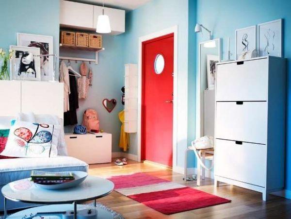 красные двери и яркий декор в коридоре однокомнатной квартиры