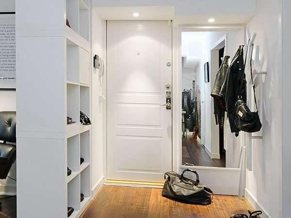 белый шкаф с открытыми полками в прихожей в скандинавском стиле