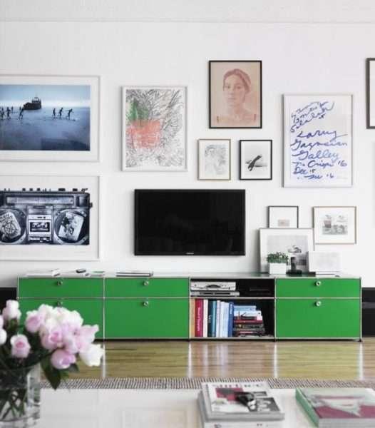 телевизор на стене гостиной с зелёной низкой стенкой