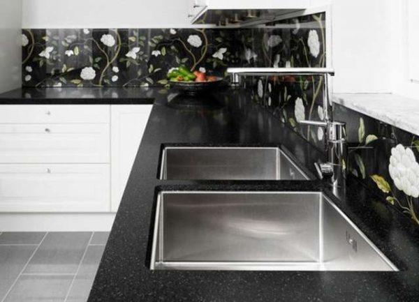 белая кухня с чёрной столешницей и фартуком с цветами