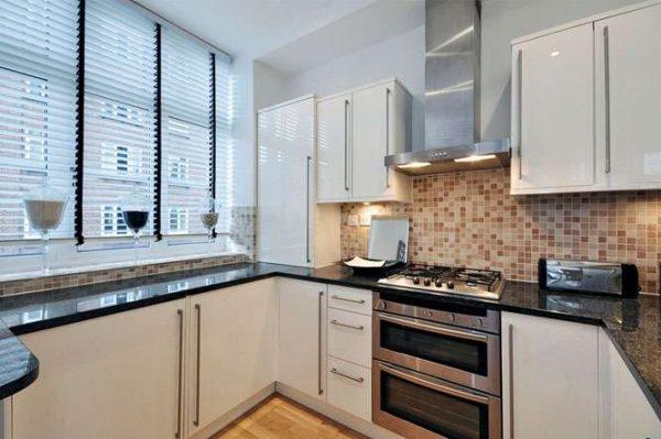 белая кухня с чёрной столешницей возле окна