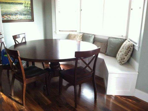 круглый стол из дерева на кухне с эркером