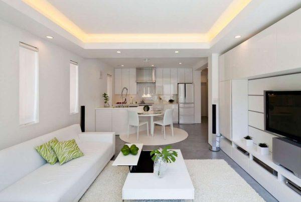 белая кухня-гостиная с глянцевыми поверхностями