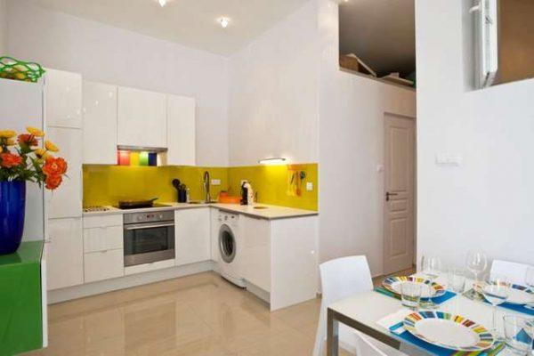 угловая белая кухня с обеденным столом в однокомнатной квартире