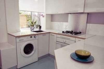 стиральная машина на кухне под подоконником