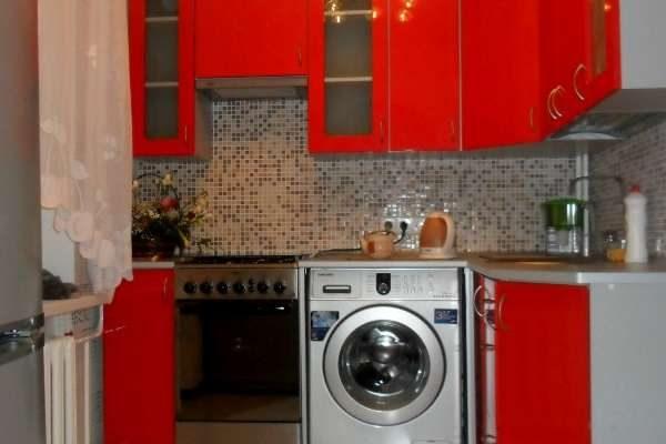 стиральная машина в интерьере кухни с красными фасадами