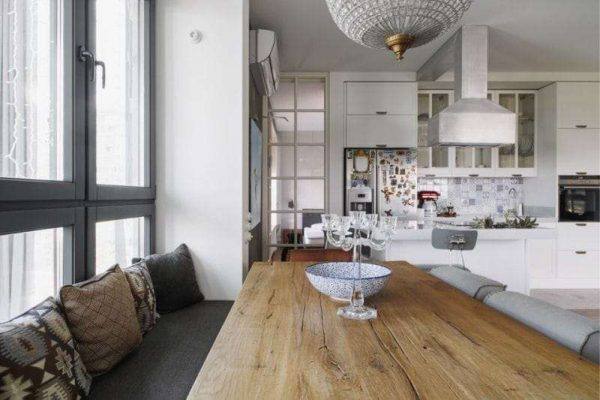интерьер кухни столовой гостиной со столом и мягким уголком