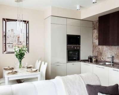 белая кухня студия с диваном и столом