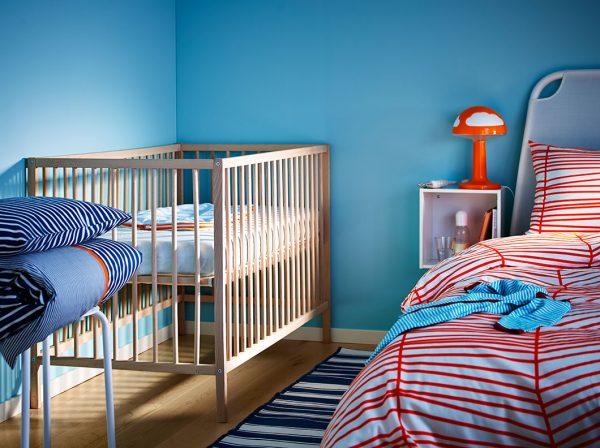 голубые стены спальни с детской кроваткой