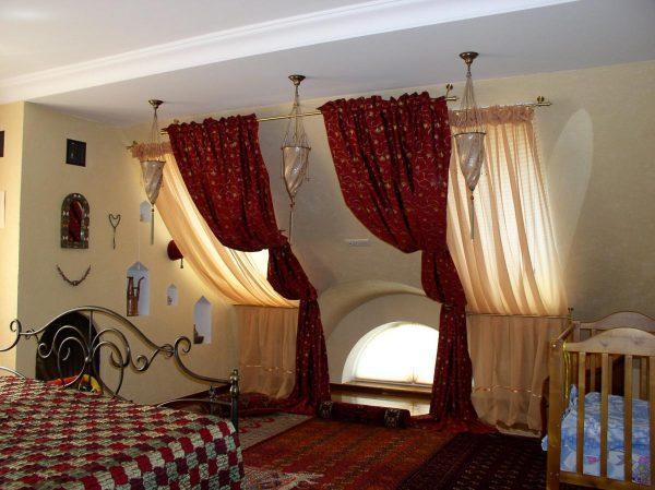 спальня в мансарде с кроваткой для ребёнка