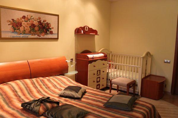 взрослая спальня с кроваткой и пеленальным столиком