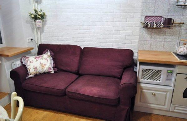 фиолетовый диван с тканевой оббивкой