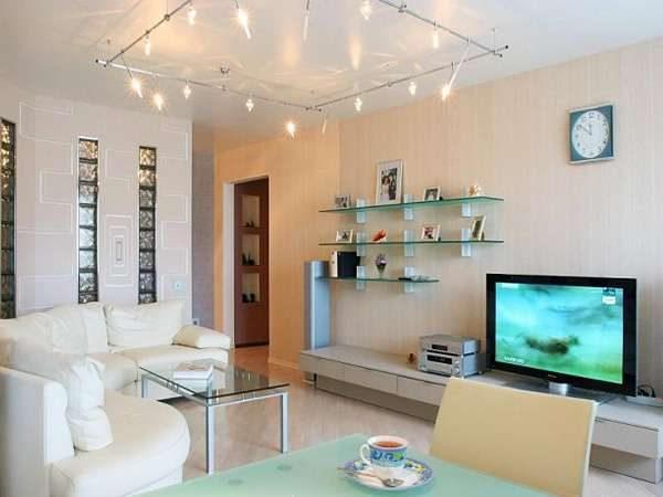 в интерьере гостиной белый угловой диван и потолочный светильник