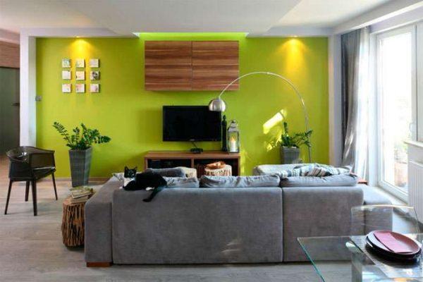 телевизор в интерьере гостиной на зелёной стене