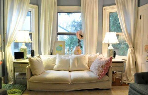 белый диван и шторы в интерьере гостиной с эркером