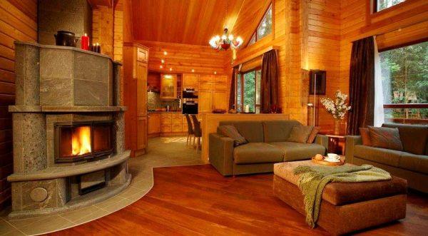камин на дровах в центре гостиной в деревянном доме