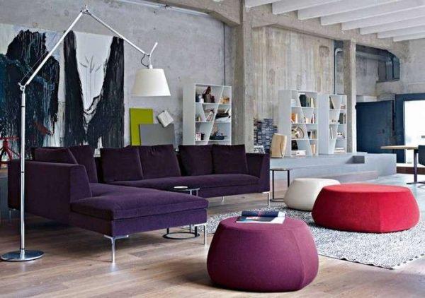 постеры и яркие пуфы в интерьере гостиной в стиле лофт