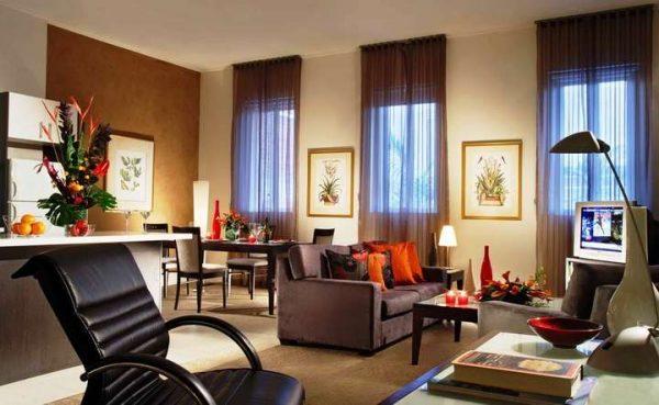 Коричневые шторы в интерьере гостиной с ярким декором