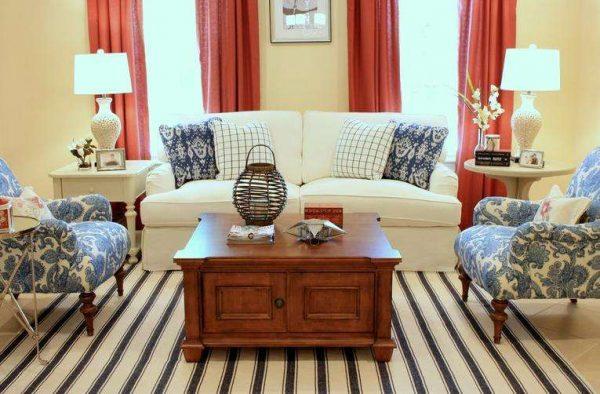 красные шторы в интерьере гостиной с белым диваном
