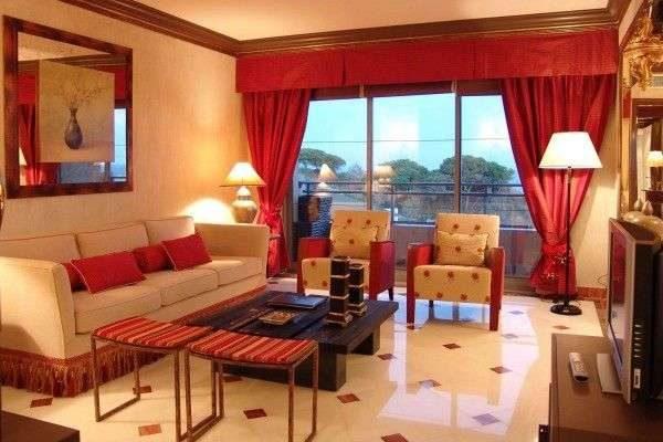 красные тяжёлые шторы в интерьере гостиной с бежевой мебелью