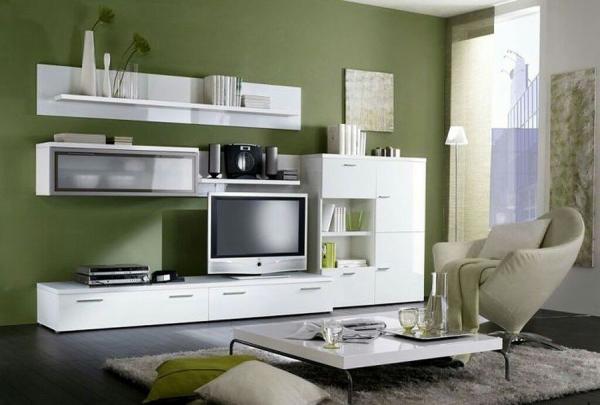 белая современная модульная стенка в интерьере гостиной с зелёными стенами