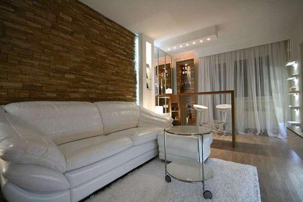 интерьер гостиной после ремонта с белым кожаным диваном
