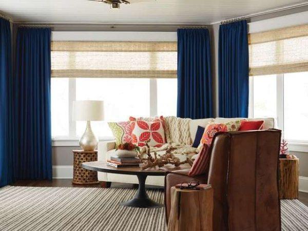 прямые синие шторы в союзе с бумбуковыми жалюзи в интерьере современной гостиной
