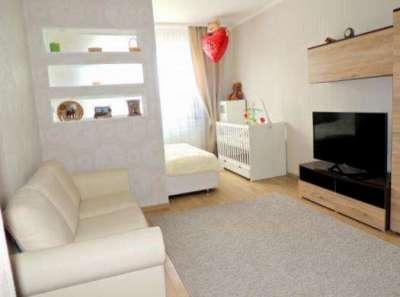 диван в светлых тонах в спальне-гостиной