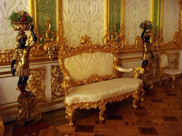диван в золотом обрамлении в прихожей в стиле барокко