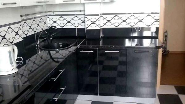 белая кухня с чёрной столешницей и фартуком