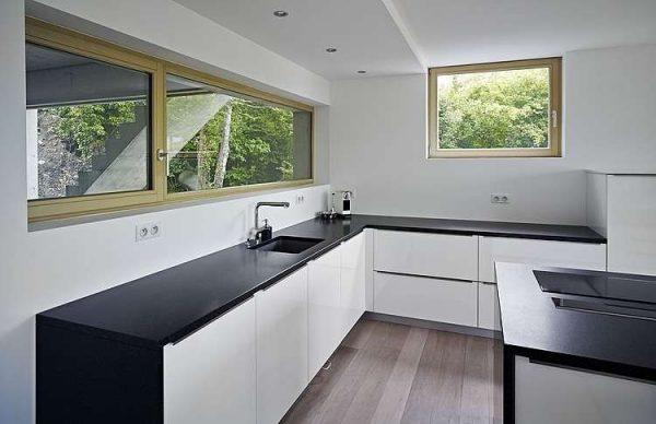 белая кухня с чёрной столешницей на нижних шкафах