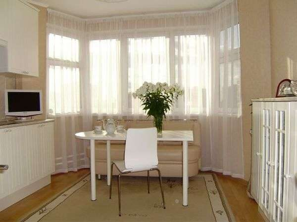 диван и столик на кухне с эркером